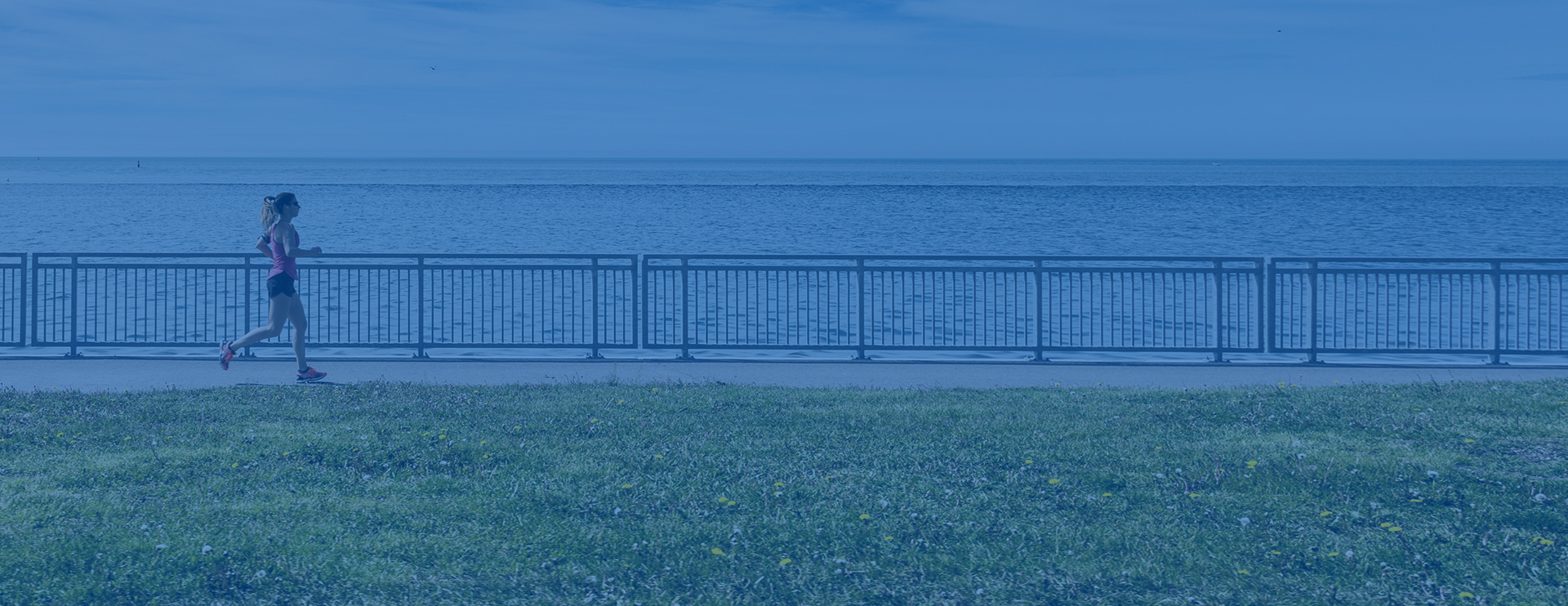 Woman running in a park area next to the ocean